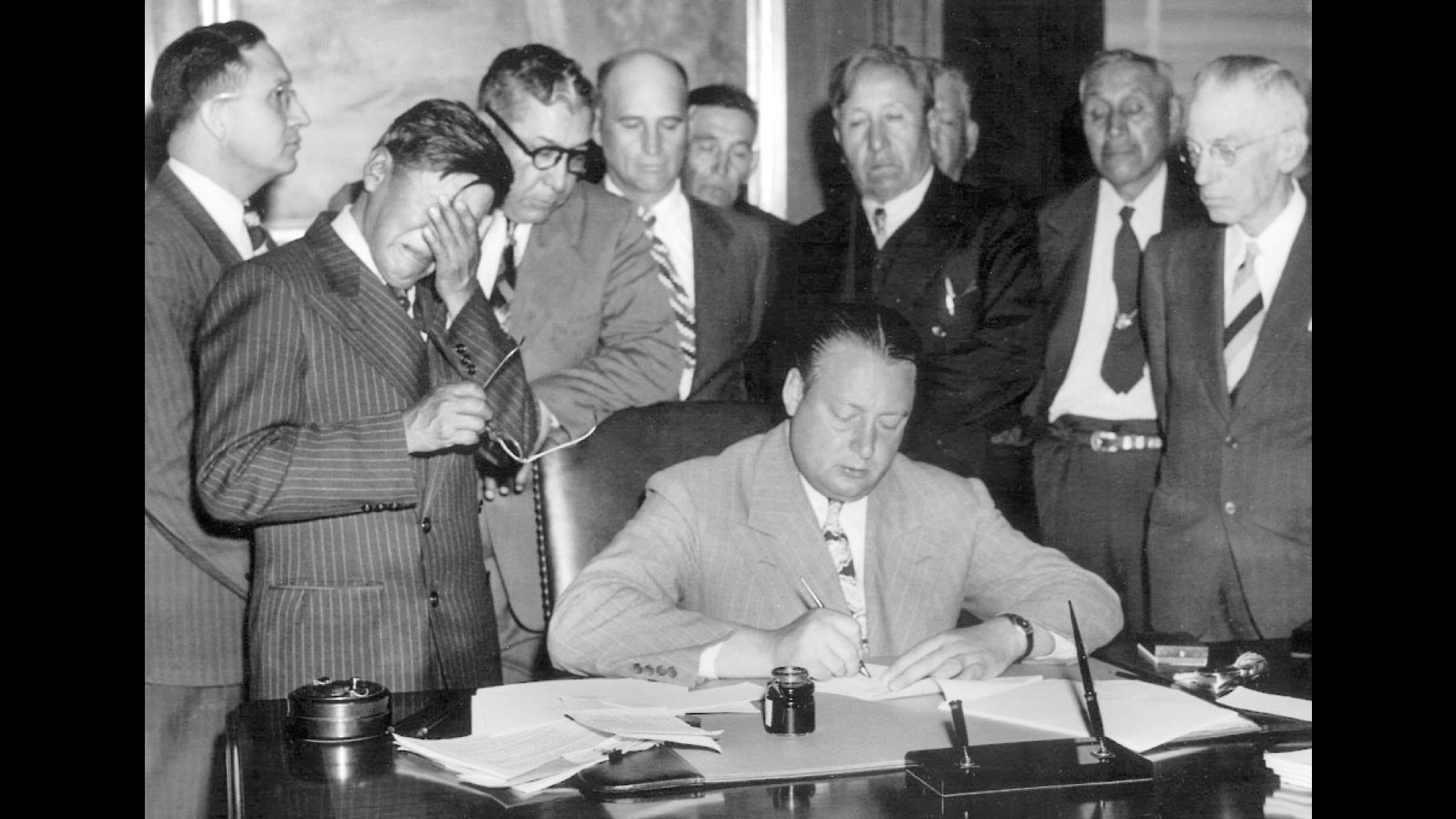 U.S. officials and representatives of the Three Affiliated Tribes (Hidatsa, Mandan, and Arikara) sign the Garrison Dam agreement on May 20, 1948. Secretary of the Interior Julius Krug writing his name while tribal chairman George Gillette sobs into his hand.